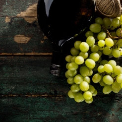Tasty Fresh Green Grape with Wine Bottle and Wine Glass Red Wine on Old Green Vintage Background Top View Horizontal Copy Space